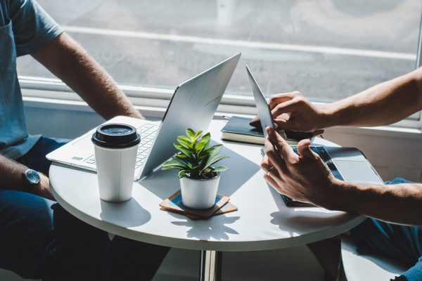Delegowanie - Dwa laptopy na małym białym stoliku kawiarnianym.