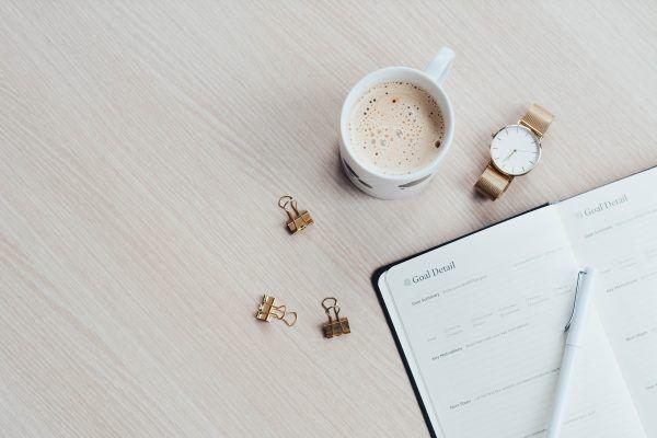 Notes z kawą i zegarkiem na drewnianym blacie stołu.