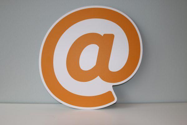 Pomarańczowy znak @ na białym tle.
