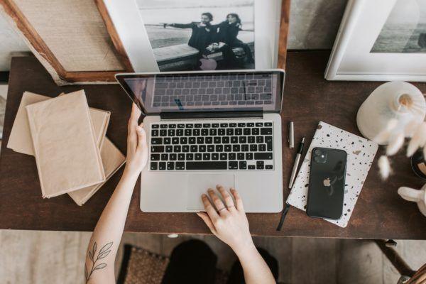 Laptop na brązowym biurku, obok telefon i notesy.