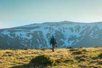 Mężczyzna na tle góry w słoneczny dzień.