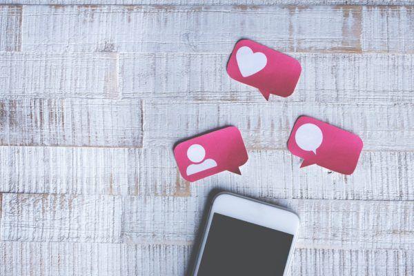 Telefon na drewnianej podłodze, nad nim popularne reakcje w social mediach.