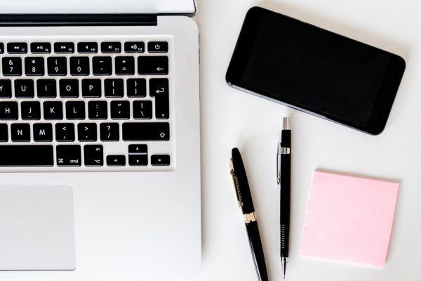 Komputer, telefon i artykuły piśmiennicze na białym blacie biurka
