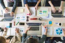 Jak zarządzać czasem? kilka osób przy biurku z dokumentami i komputerami