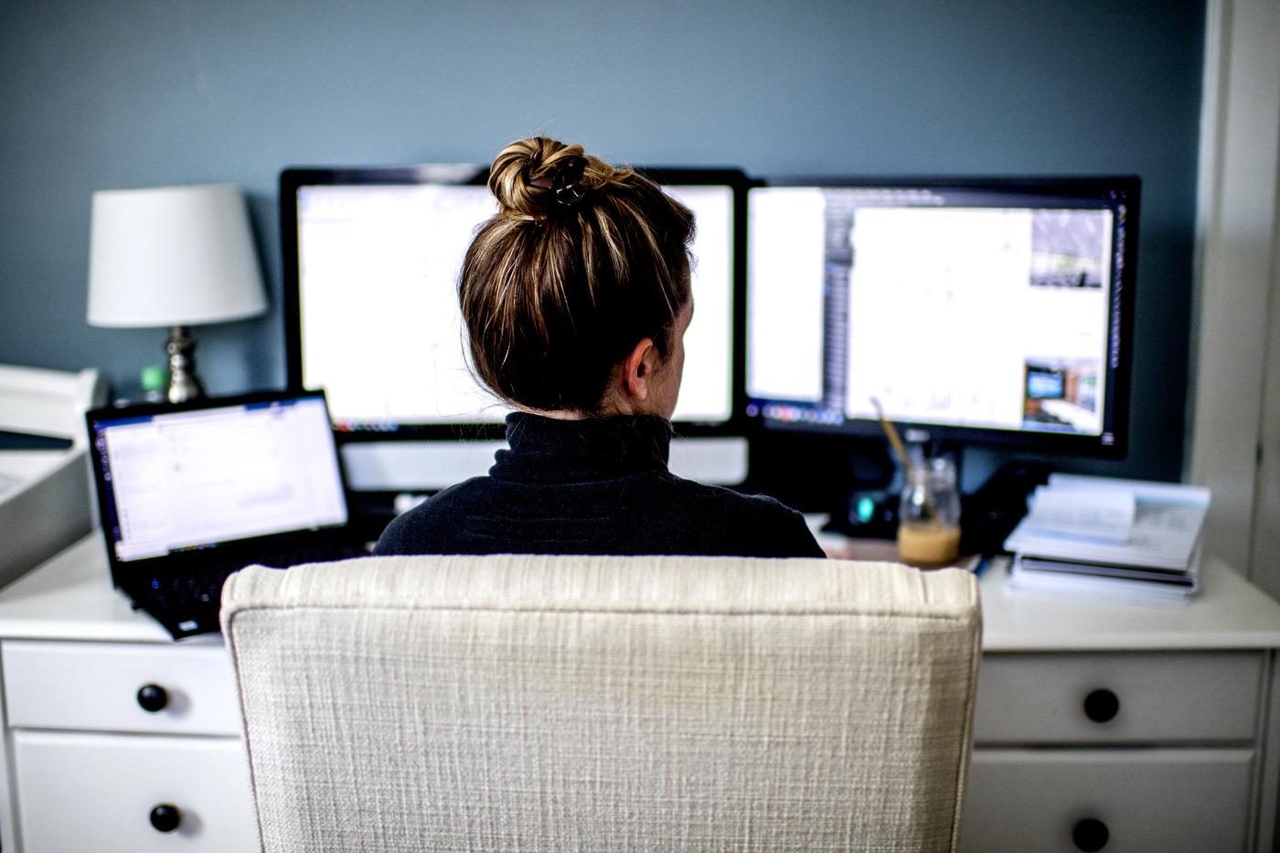 kobieta przed trzema monitorami